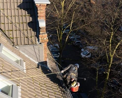 Reinigung der Dachrinne auf dem Dach mit Sicherung am Dachfenster