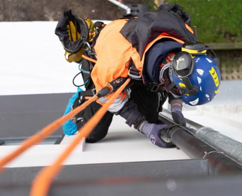 Blitzschutzmontage an einem Fallrohr durch Kletterer